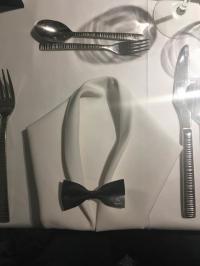Phantasievoll gestaltete Stoffserviette mit Fliege aus Papier bei einem Galadinner; Bild Hotelier.de