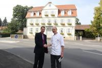 """Alexander Hess (links) und Thomas Raabe vor dem Poststation Zum Alten Forstamt""""; Bildquelle Compass Group Deutschland GmbH"""