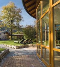 """Vom verglasten Ruheraum der Badelandschaft schweift der Blick in den herrlichen Landschaftspark und auf die """"Alm im Park"""" mit zwei Junior-Suiten"""