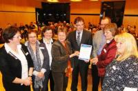 Franz-Josef König übergibt im Beisein der Ministerin das SERQUA Zertifikat / Bildquelle: Gesellschaft für Systemisches Management