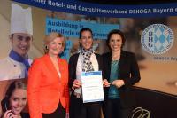 """Angela Inselkammer (links) und Christine Haderthauer (rechts) überreichen Kathrin Wickenhäuser, die kunde zum offiziellen """"Ausbildungsbotschafter der bayerischen Hotellerie und Gastronomie"""" / Bildquelle: Wilde & Partner"""