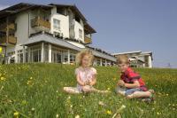 Kinder beim Spielen in der Wiese vor dem Hotel / Bildquelle: Kinderhotel Oberjoch