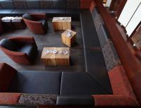 Noble Geste: Die Raum umlaufende Loungegruppe 40880 (Bänke beliebig kombinierbar) setzt sich mit edlen rot-schwarzen Jacquard- und Lederbezügen gekonnt in Szene. Sessel Havanna, Modell 1145 setzt sich mit edlen rot-schwarzen Jacquard- und Lederbezügen
