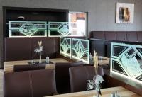 Edel, fast unsichtbar und doch privat wirken die einzelnen Sitzbereiche dieses Restaurants in Heide durch die mit Motiven aus der Stadt versehenen Glasscheiben