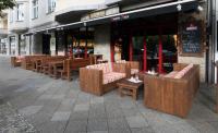 Perfekter Look - Outdoor Möblierung mit Thermoholz: vorn rechts die Loungesofas Modell 40982, dazu der Couchtisch 30110, in der Mitte schlichte Bänke, Modell 40980 und Tisch Modell 30111. (Location: Pirate Pizza Berlin)