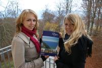Janet Riebe und Jeannette Brussig von der Tourismuszentrale Rügen mit dem Rügenkatalog 2012 am Nationalpark-Zentrum Königsstuhl (Bildnachweis: Tourismuszentrale Rügen)