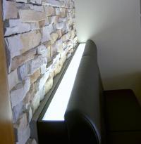 Eine gern gewählte Lösung: Hinter der Bank wird ein Lichtband integriert, das sanft nach oben abstrahlt und die Struktur der Wand elegant betont