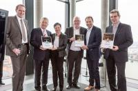 Mathias Hansen überreicht die Auszeichnungen an die Preisträger. Die Geschäftsführer Roland Gilges und Dirk Hunke (2. und 3. v.r.) freuen sich über den ersten Platz / Bildquelle: Blue Moon CC GmbH