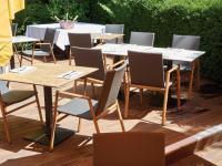 Auf der Terrasse kommen komfortable Armlehnstühle in Teakholzoptik zum Einsatz. / Bildquelle: GO IN GmbH
