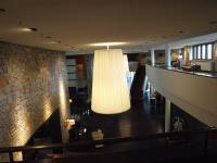 Der Blick von der 1. Etage auf den Eingangsbereich samt Naturstein und schönen Hängeschirmlampen / Bildquelle: Sascha Brenning - Hotelier.de