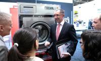 Stellte auch Sascha Brenning von Hotelier.de (Sales & Marketing, ganz rechts) während der Internorga die neuen Waschmaschinen vor: Jürgen Schäfer, Leiter Wäschereitechnik bei Miele Professional.