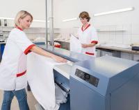 Kann bei Bedarf von zwei Personen bedient werden: Die neue Mangel PM 1217, die bis zu 60 Kilogramm Wäsche pro Stunde glättet / Bildquelle: Miele