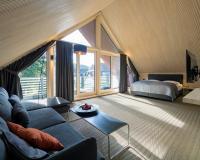 In den Suiten schaffen die großformatigen Dachbauteile LIGNO Block Q Akustik mit ihren sichtbaren profilierten Echtholzflächen bis unter den Dachfirst ein ganz besonderes Innenraumerlebnis