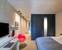 In den EG-Zimmern sind die Badezimmer als schwarze Kuben in den Raum eingestellt — Kontrapunkte zu den Wänden und Decken in Schwarzwälder Weißtanne