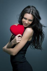 Valentine's day - beautiful smiling woman with a gift in the form of heart in his hand