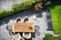 Sonnige Terrasse mit geschickter Kombination aus Korbsesseln und Metallstühlen am rustikalem Holztisch und Liege
