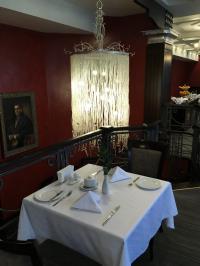 Gemütlicher 2-er Restaurant-Tisch an einer Balustrade mit hübschem Kristall-Lüster und Bild im Hotel Chichikov in Charkiv/Ukraine