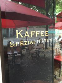 Kaffeespezialitäten - der Siegeszug der schwarzen Bohne als Schriftzug im Spiegelbild eines Restaurants in Babelsberg/Potsdam
